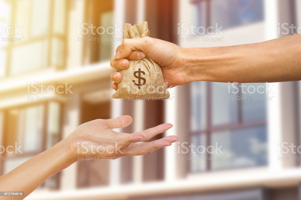 A man hand holding a money giving to another person for buying real estate. Loans for real estate concept. Conceptual give money to someone else to exchange real estate. stock photo