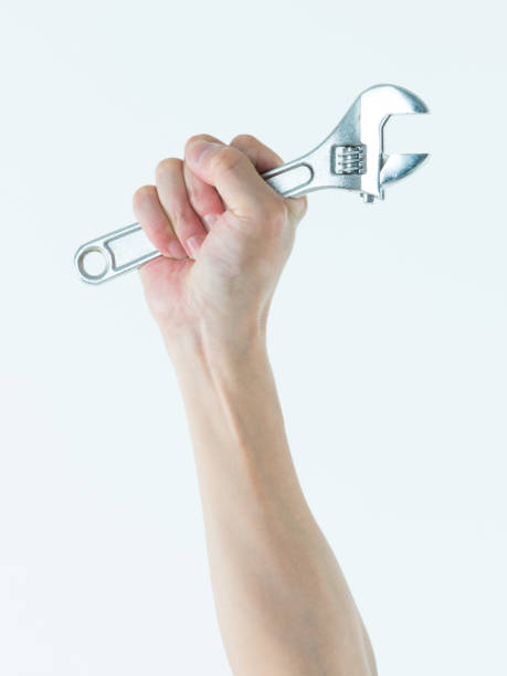 Man hand holding a wrench on white background stock photo