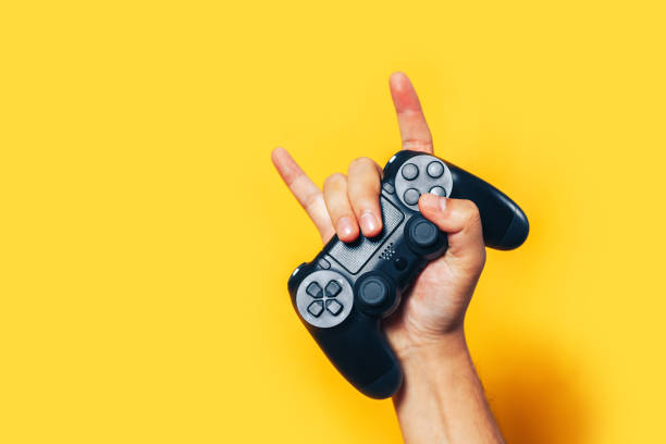 Man hand holding black gamepad Man hand holding black gamepad show cool symbol on yellow background, minimalism concept. gamepad stock pictures, royalty-free photos & images