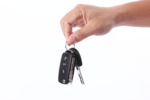 Man hand holding car key, isolated on white background