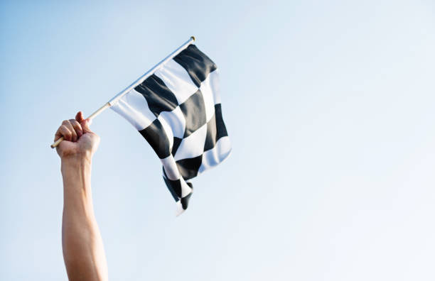 Man hand holding checkered flag in the wind Man hand holding checkered flag in the wind. starting line stock pictures, royalty-free photos & images