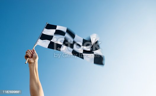 Man hand holding checkered flag in the wind.