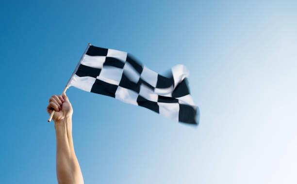 Mann Hand hält karierte Flagge im Wind – Foto