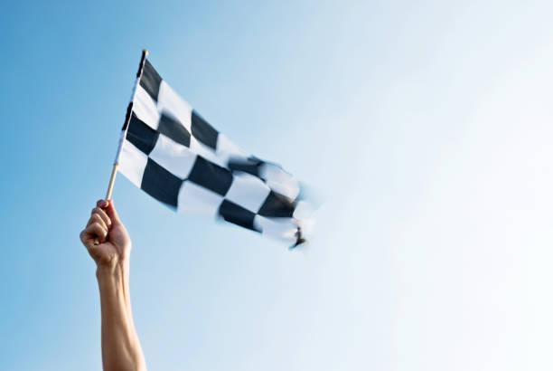 man hand holding checkered flag in the wind - finishing stock photos and pictures