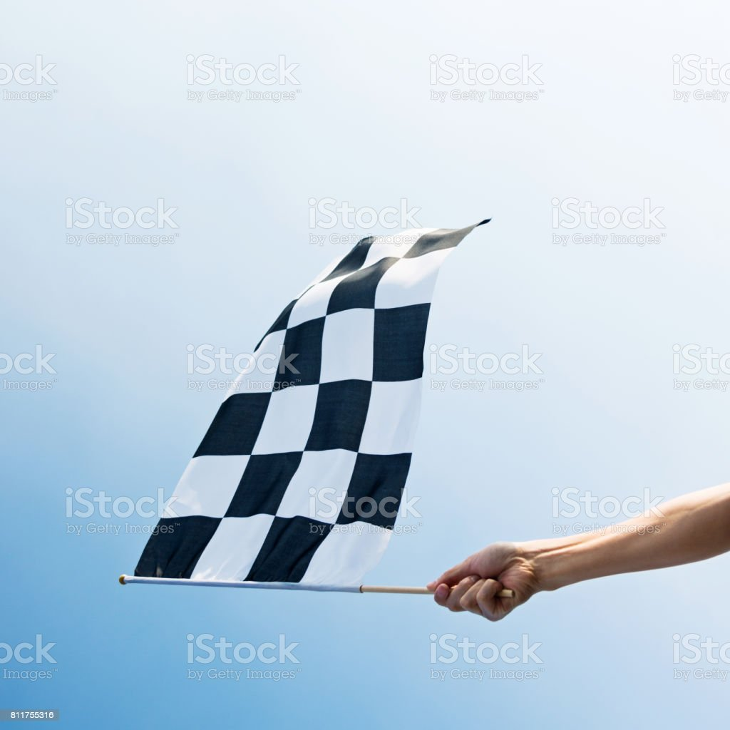 Man hand holding checkered flag in the wind stock photo