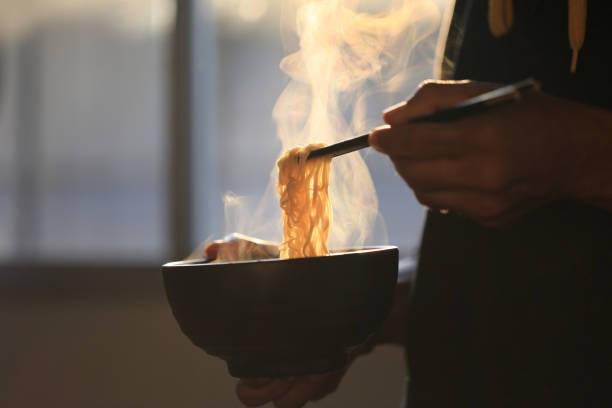 家の中で煙が上がっている木のボウルにインスタント麺の男手保持箸、ナトリウムダイエット高リスク腎不全、健康的な食生活の概念 - ラーメン ストックフォトと画像