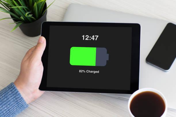mann hand mit tablet-computer mit batterie auf dem bildschirm - sinnvolle wörter stock-fotos und bilder