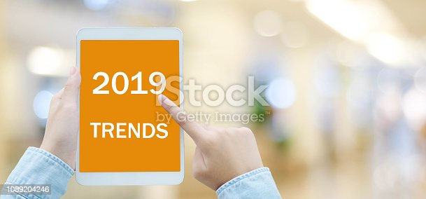 istock Man hand holding digital tablet with 2019 trends on screen background, digital marketing, business and technology concept 1089204246