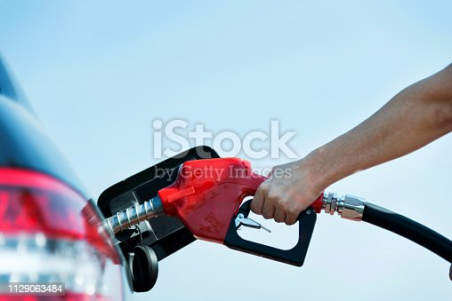 Man hand holding fuel pump and refilling car