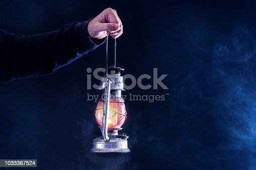 Man hand holding gas lantern on dark and night smoked foggy background. Gas or oil lamp burning. Horror and Halloween concept. Close up, selective focus.