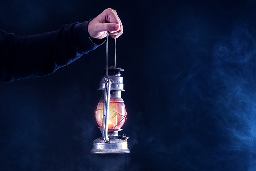 Man hand holding gas lamp on dark and night smoked foggy background