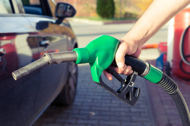 Man hand holding gasoline pump in a gas station Man hand holding gasoline pump in a gas station ready to fill the tank or to refuel as expensive fuel concept with price rising biofuel stock pictures, royalty-free photos & images