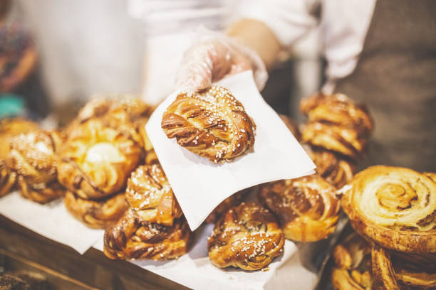 Man hand holding golden colored pastry rolls in bakery. Close up of baker hand holding puff pastry stuffed with cheese. pastry dough stock pictures, royalty-free photos & images