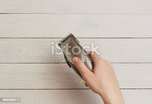 866388950istockphoto Man Hand holding hair clippers on white wooden background 866388674