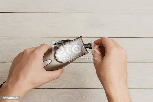 866388950istockphoto Man Hand holding hair clippers on white wooden background 866388680