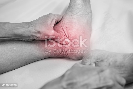 1133511905istockphoto man hand holding he healthy foot and massaging ankle 612848788