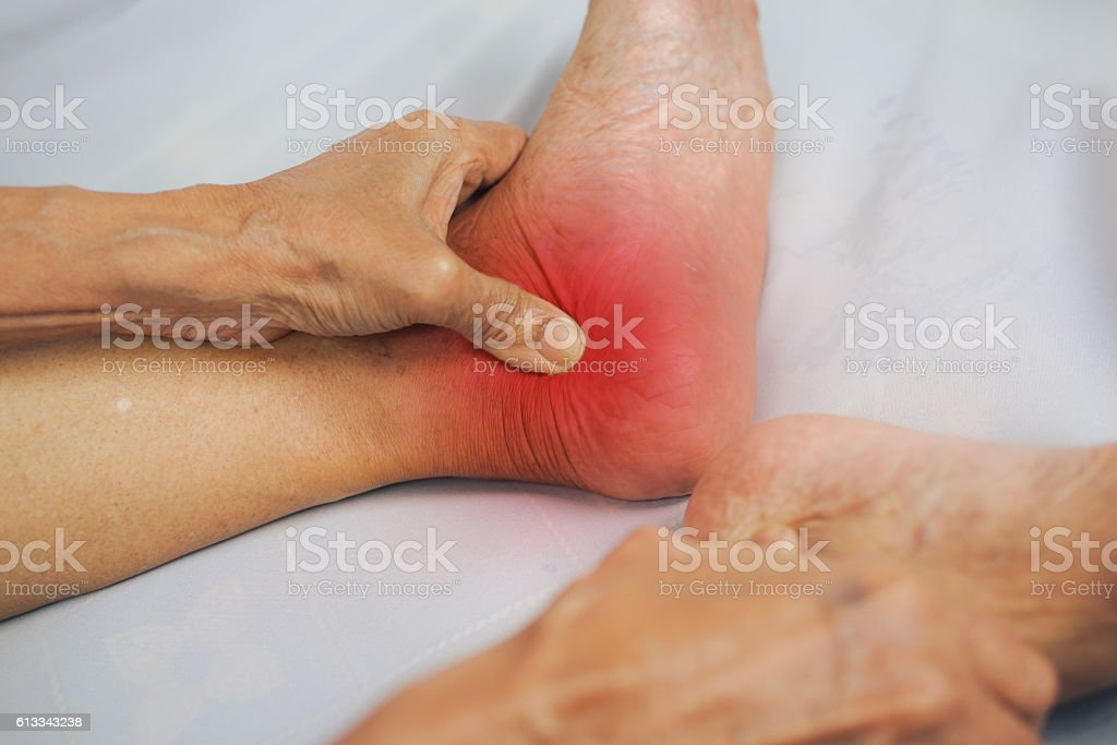 man hand holding healthy foot and massaging ankle stock photo