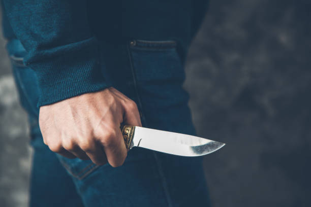 man hand holding knife on abstract background stock photo