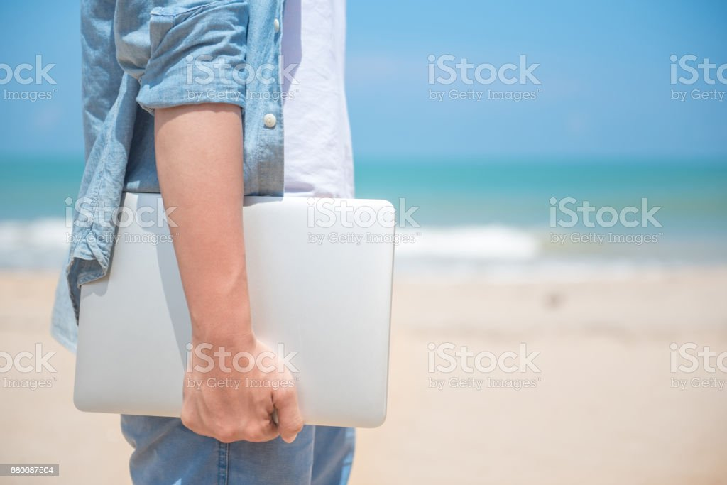 Man hand holding laptop at the beach stock photo