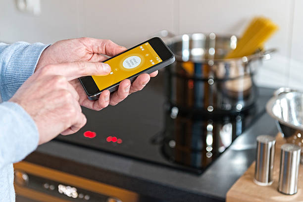 Man hand holding mobile phone smart control home cooker, kitchen – Foto