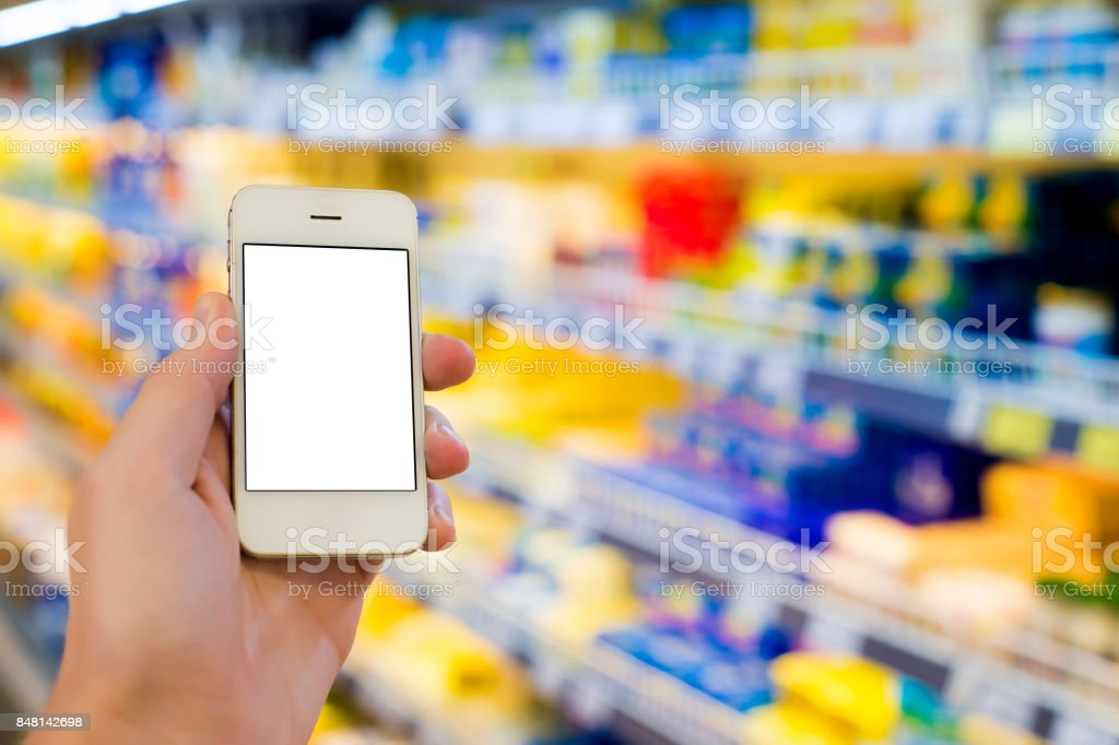 Man hand holding mobile smart phone on Supermarket blur background, business concept stock photo
