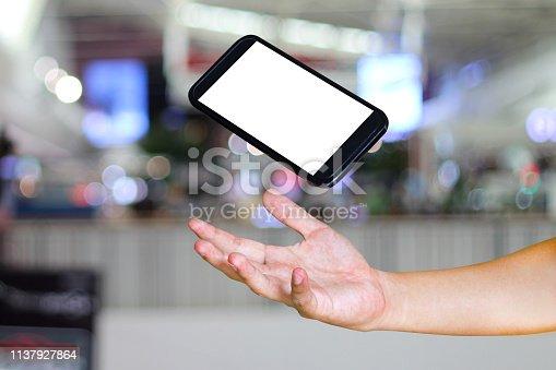 istock Man hand holding modern smartphone on Blurred background , mock-up smartphone 1137927864