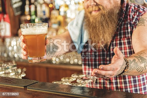 istock Man hand holding out drinks in pub 677519650