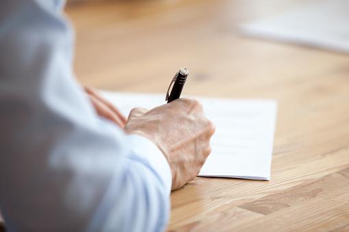 Man hand holding pen, writing notes at meeting close up