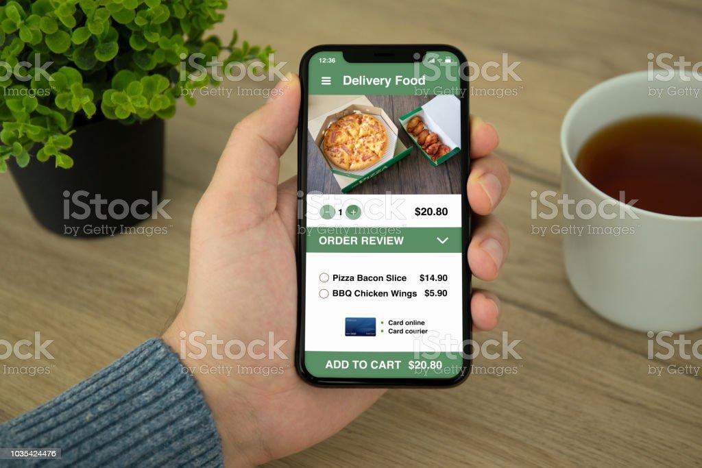 Mann Hand hält Handy mit app-Sushi-Lieferservice – Foto