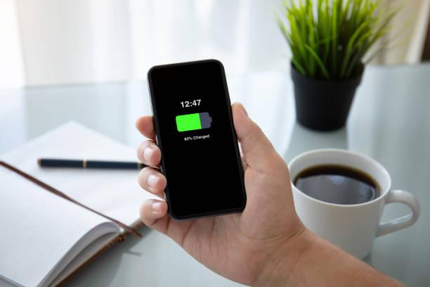 mann hand hält telefon mit aufgeladenen akku auf dem bildschirm - sinnvolle wörter stock-fotos und bilder