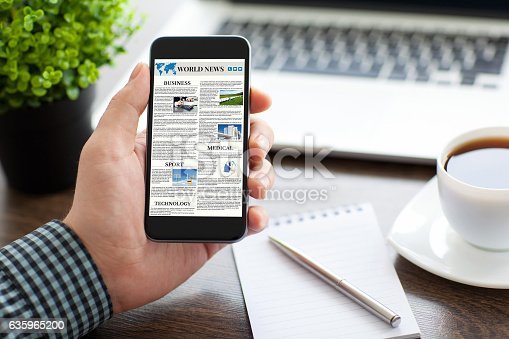 istock man hand holding phone with world news site on screen 635965200