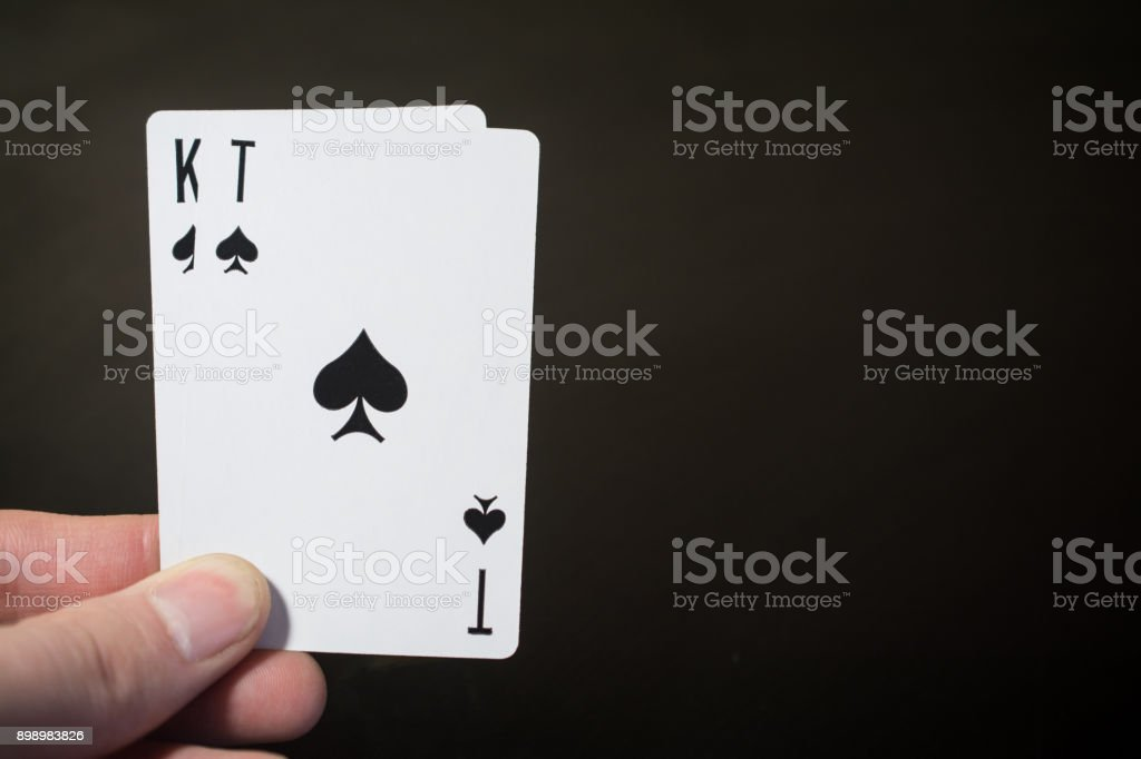 Man hand holding playing card ace and kind of spades isolated on black background with copyspace abstract – zdjęcie