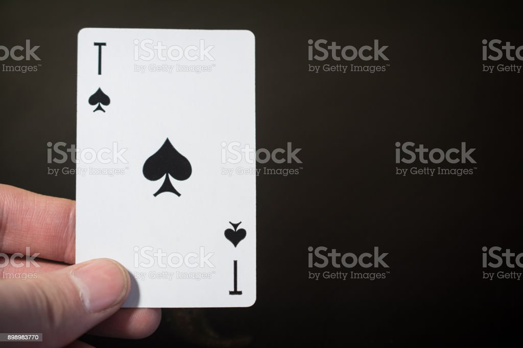 Man hand holding playing card ace of spades isolated on black background with copyspace abstract – zdjęcie