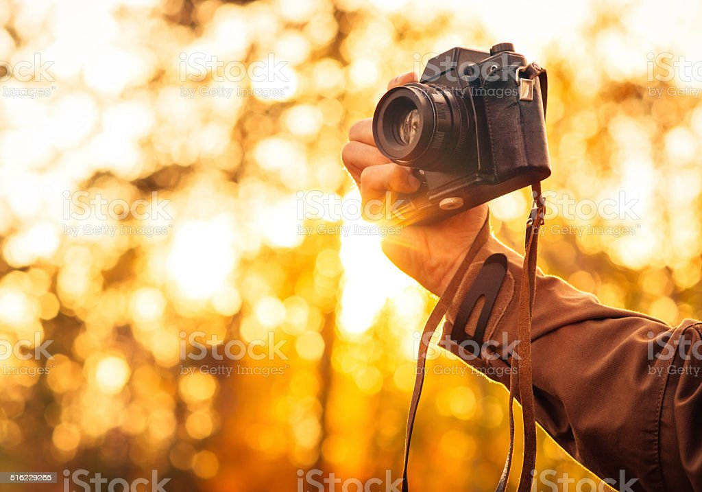 Man hand holding retro photo camera outdoor Lifestyle concept stock photo
