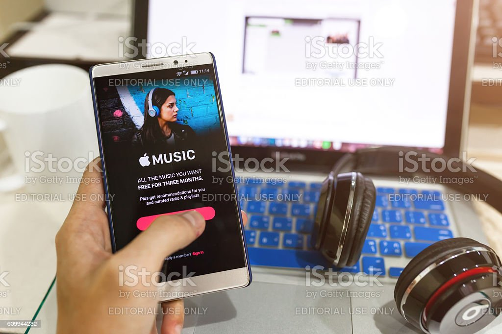 Man hand holding screen shot of Apple music app showing stock photo