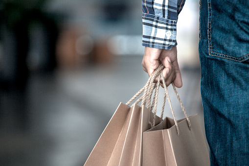 Man hand holding shopping bags on the street in the shopping mall in vintage color tone