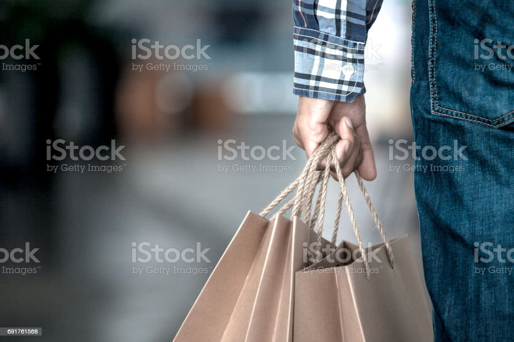 Man hand holding shopping bags on the street in the shopping mall стоковое фото