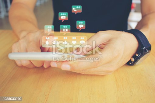 Man hand holding smart phone with hologram or icon of set of social media on the wooden table in restaurant, Communication technology and Social media concept
