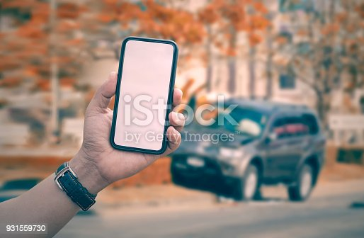 istock man hand holding smartphone with car crash accident background 931559730