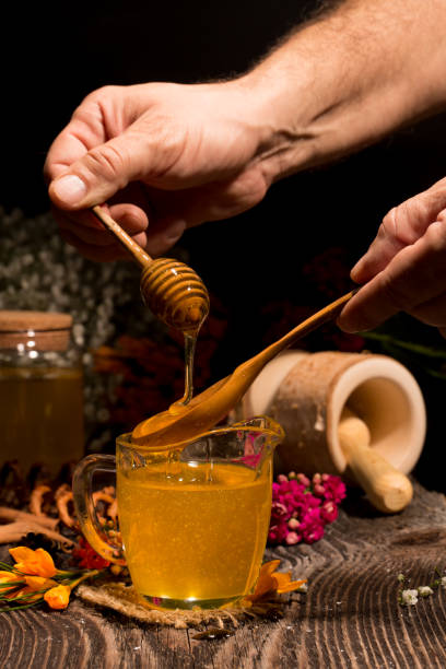 Man hand holding wooden honey dipper, honey spoon on top of glass of tea and dripping honey in hot tea stock photo