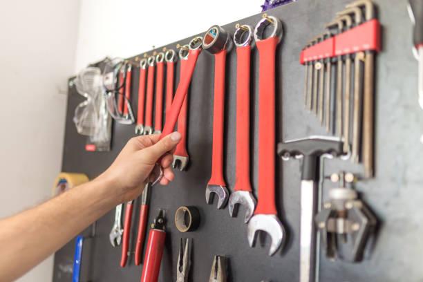 Mano de hombre sosteniendo la llave inglesa. Otras herramientas en la pared. - foto de stock
