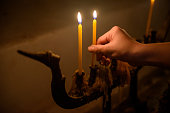 Man hand holding yellow candle