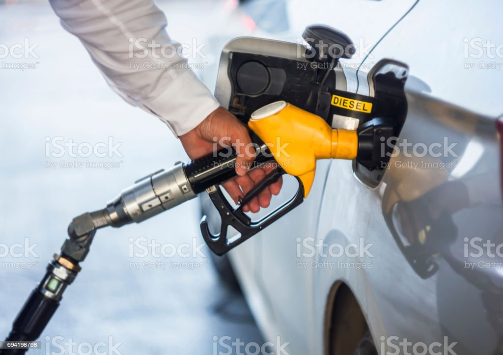 Man hand holding yellow petrol pump stock photo