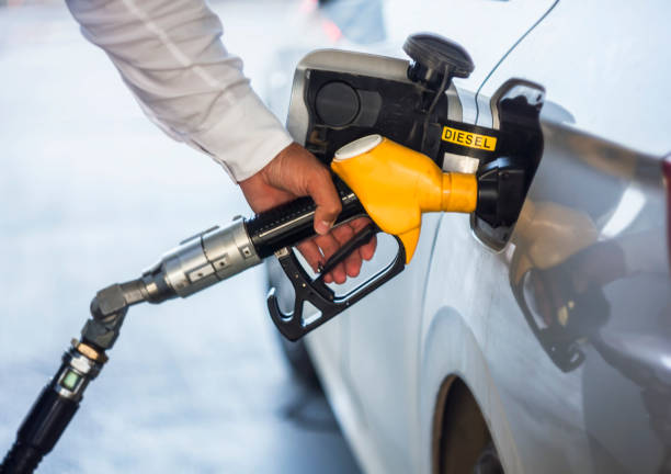 Man hand holding yellow petrol pump Man hand holding yellow petrol pump, pump inside the car. diesel stock pictures, royalty-free photos & images