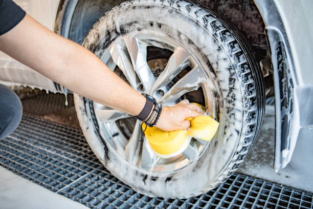 man hand holding yellow sponge cleaning car stock photo