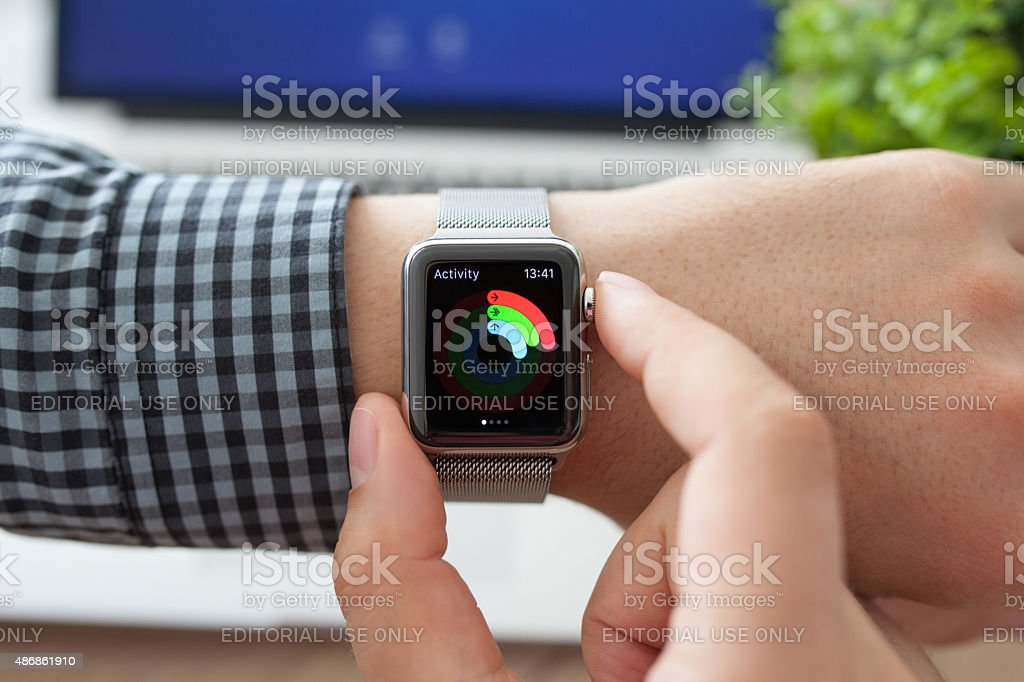 Man hand in Apple Watch with app Activity and Macbook stock photo