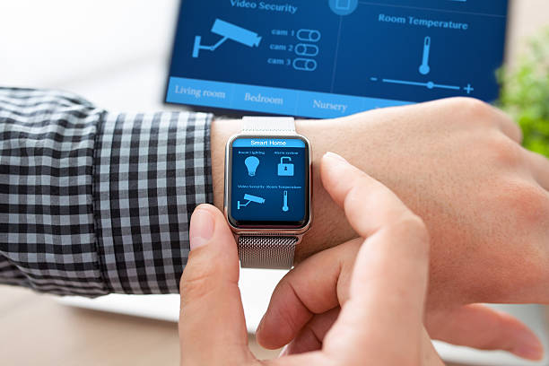 man hand in watch with smart home and computer man hand in watch with program smart home on the screen against the background of computer smart thermostat stock pictures, royalty-free photos & images