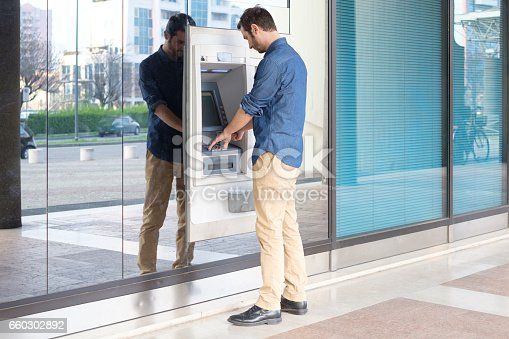 istock Man hand inserting a credit card in an atm 660302892