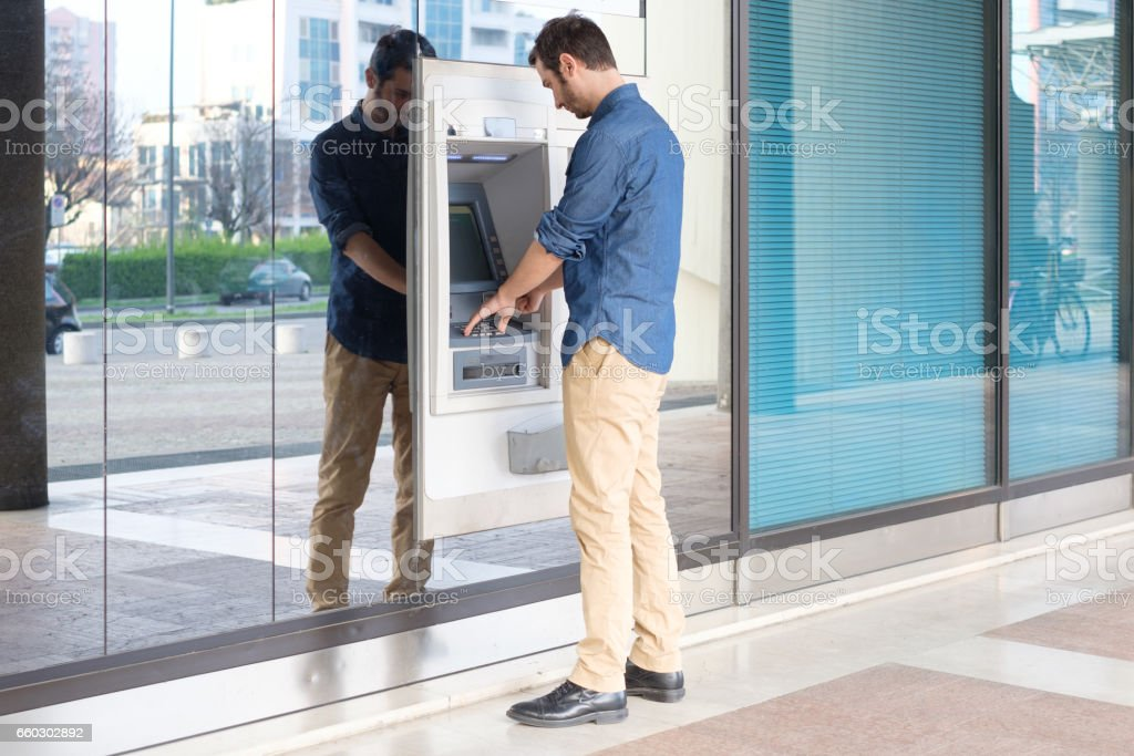Man hand inserting a credit card in an atm stock photo