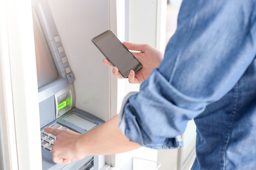 istock Man hand inserting a credit card in an atm 661692120